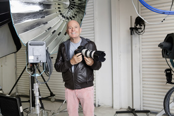 Portrait of happy senior photographer with camera in studio