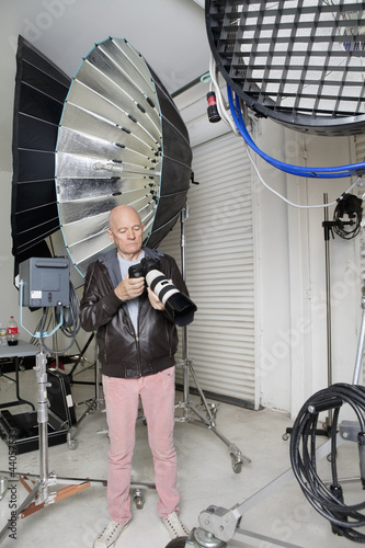 Senior photographer with camera in studio