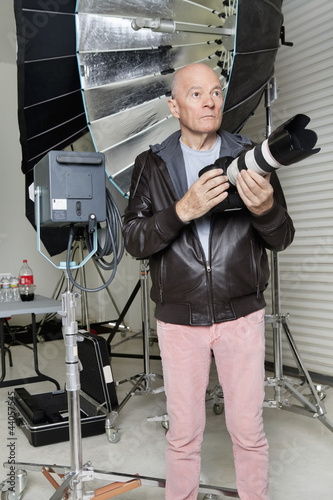 Front view of senior man with camera in photographer's studio