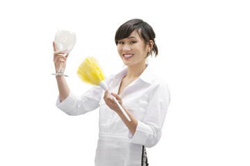 Portrait of a happy female house cleaner dusting glass with feather duster over white background