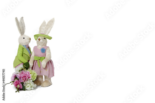 Rabbit couple with flower bouquet standing over white background