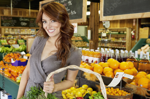Portrait of a happy brunette woman standing with basket in fruit market