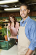 Portrait of a happy young sales clerk holding vegetables with woman in background