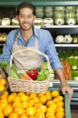 Portrait of a happy man with vegetable basket standing near oranges stall in supermarket