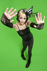 Portrait of young woman posing with fingerless gloves and headdress over green background