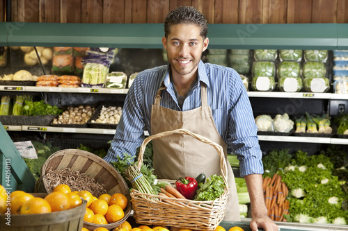 Portrait of a happy young salesman with vegetable basket in supermarket