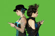 Side view of punk females standing back to back over with mobile phones over green background