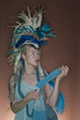 Beautiful young woman wearing costume with feather headgear over colored background