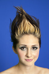 Portrait of a beautiful young woman with spiked hair over colored background