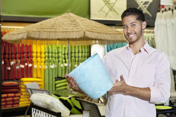 Happy young man holding a souvenir in store