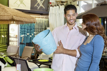 Happy young couple looking at each other while man holding a souvenir in store