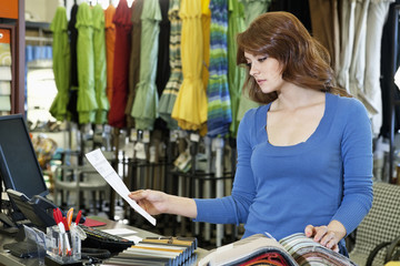 Beautiful young woman looking a paper while selecting textile sample in store
