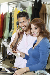 Portrait of a happy couple with man with telephone receiver and woman with paper in store