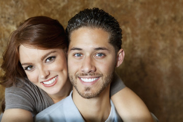 Close-up of beautiful young woman hugging man from behind