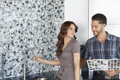 Beautiful young couple standing model home kitchen with color samples