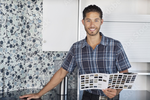 Portrait of young man with color samples standing in model home kitchen