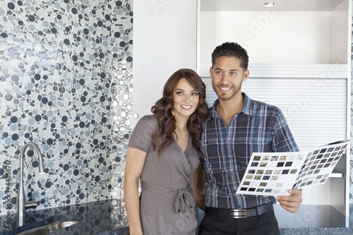Beautiful happy couple with color samples in modern kitchen