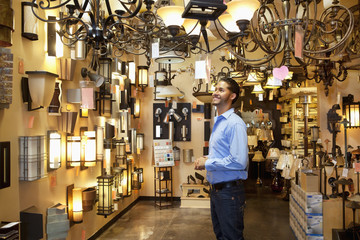 Happy young man browsing for lights fixture in store