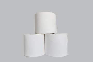 Stacks of rolls of toilet paper on white background
