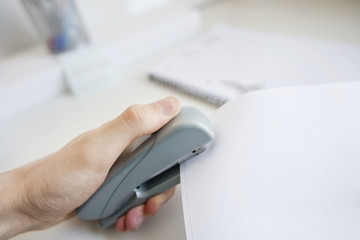 Close-up of man's hand stapling paper in office