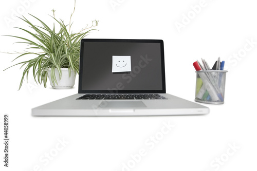 Smiley face sticky note on laptop with office supplies and pot plant