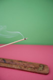 Close-up view of incense stick burning over colored background