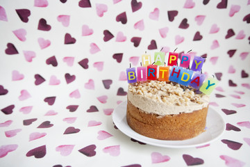 Close-up of birthday candles on cake over heart shaped background