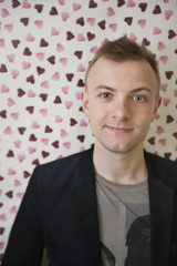 Portrait of young man smiling over heart shaped wallpaper
