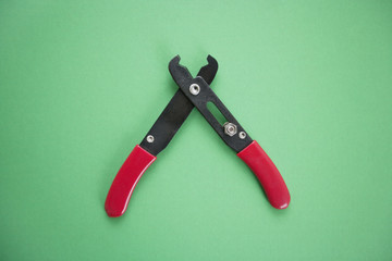 Close-up view of duckbill pliers over green background