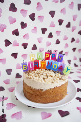Close-up of birthday cake with candles over heart shaped background