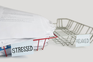 Stack of paperwork in stressed tray with empty relaxed platter over white background