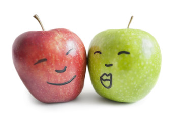 Red and green apples with face over white background