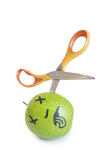 Granny smith apple murdered by scissor over white background