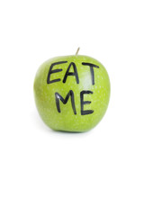 Close-up of text on a granny smith apple reading eat me over white background