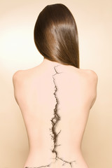 Bare back of woman with a crack on spine over colored background