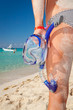 Woman in bikini with snorkeling mask standing on Caribbean beach
