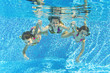 Happy family underwater in swimming pool, fun on summer vacation