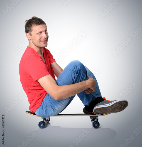 Cool man sitting on a skateboard deck
