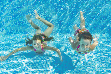 Happy smiling underwater children in swimming pool, kids sport