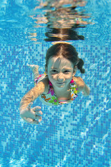 Happy smiling underwater child in swimming pool, summer vacation