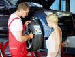 Mechanic in a garage explaining tyre labeling to a customer