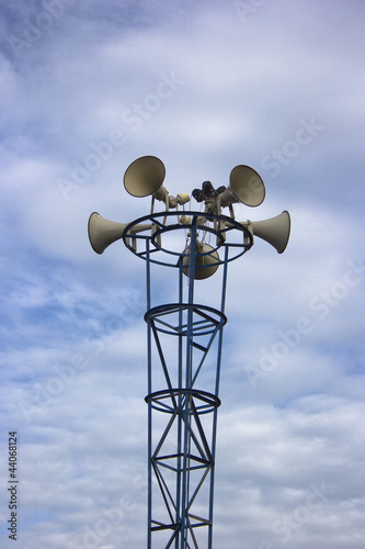 many loudspeaker againt cloudy blue sky background