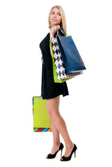 Young happy woman in black dress with colorful shopping bags on