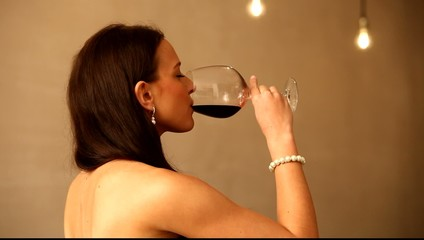 Happy young woman with glass of red wine.