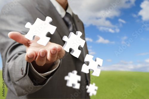 businessman hand and business puzzles as concept