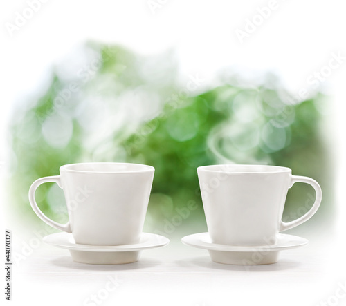 Cups of hot drink on defocus summer background