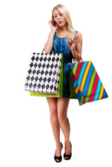 Young woman with shopping bags and mobile phone on a white backg