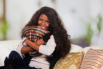 African lady with cushion sitting on the sofa