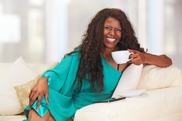 African lady with cup of coffee sitting on the sofa