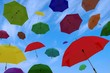 flying of multicoloured umbrellas on blue sky with clouds